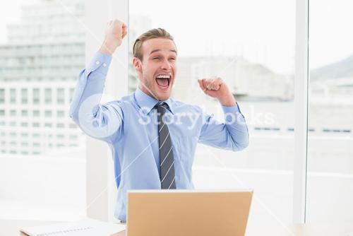 Smiling businessman cheering with arms up