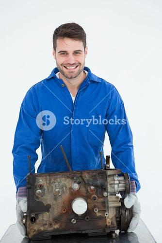 Smiling male machanic carrying old car engine