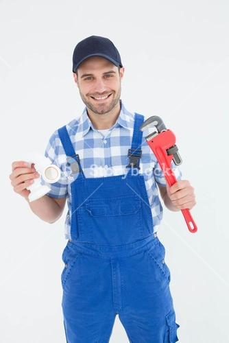 Plumber holding adjustable wrench and sink pipe