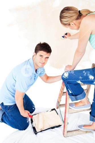 Beautiful couple painting a room