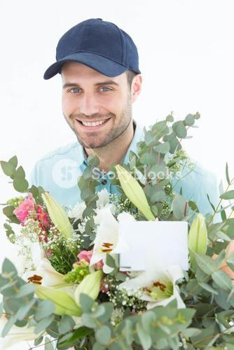 Happy delivery man with bouquet