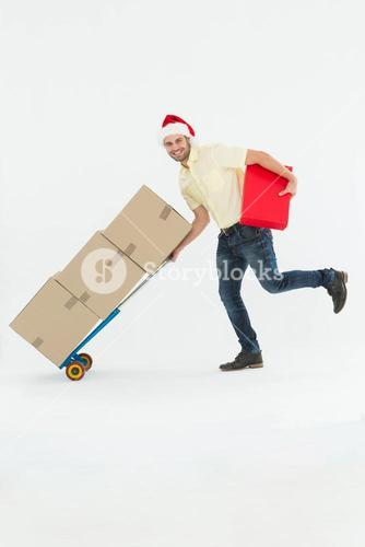 Delivery man pushing trolley of boxes during Christmas