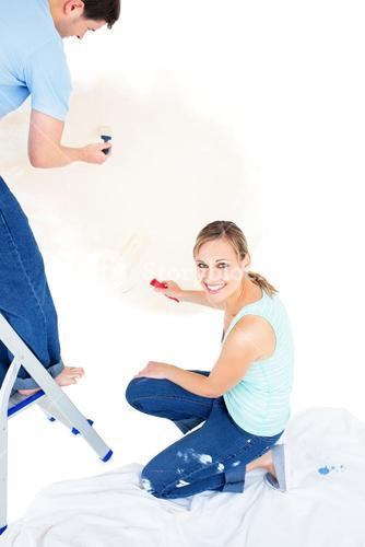 Serious couple painting a room