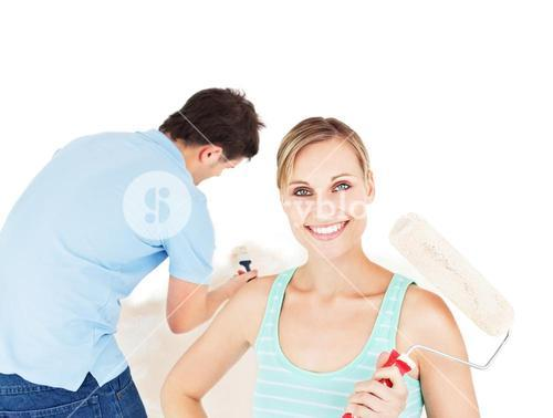 Bright couple painting a room