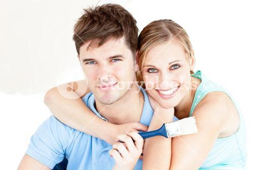 Smiling couple painting a room