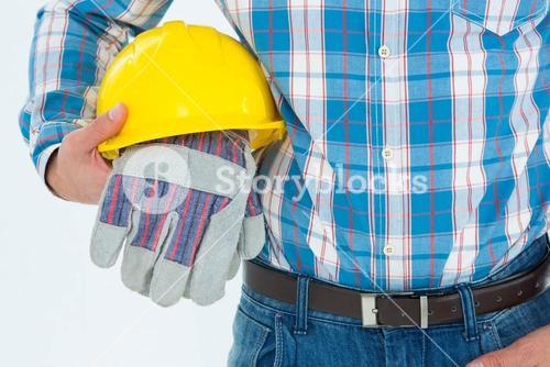 Construction worker holding hard hat and gloves