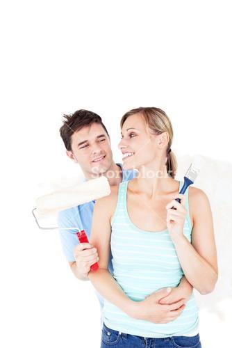Loving young couple painting a room