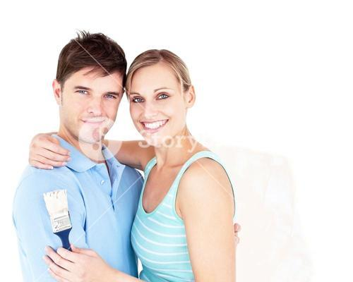 Happy young couple painting a room
