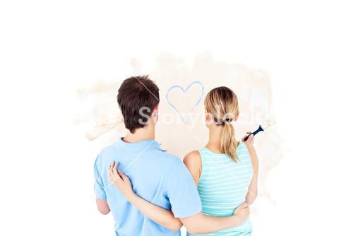Kind young couple painting a room