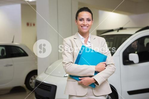 Businesswoman holding document while looking at camera
