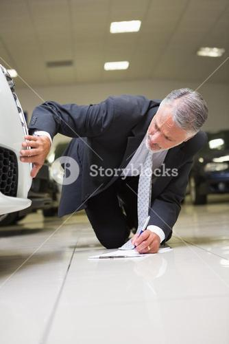 Man looking at the bumper while writing on clipboard
