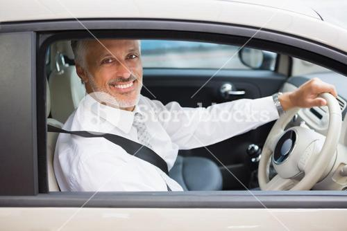 Smiling businessman sitting at the wheel of a car for sale