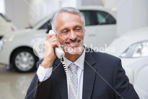 Smiling businessman making a phone call