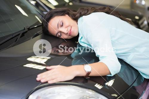 Smiling woman hugging a black car