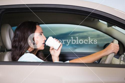 Smiling woman driving car while drinking coffee