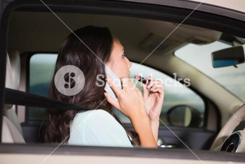 Woman using mirror to put on lipstick while on the phone