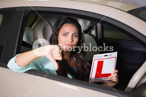 Woman gesturing thumbs down holding a learner driver sign