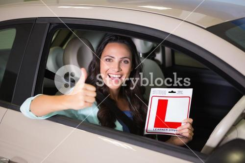 Woman gesturing thumbs up holding a learner driver sign