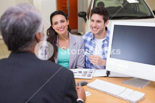 Smiling couple holding credit card to buy a car