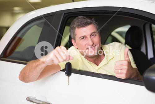 Positive customer holding a key sitting in his car
