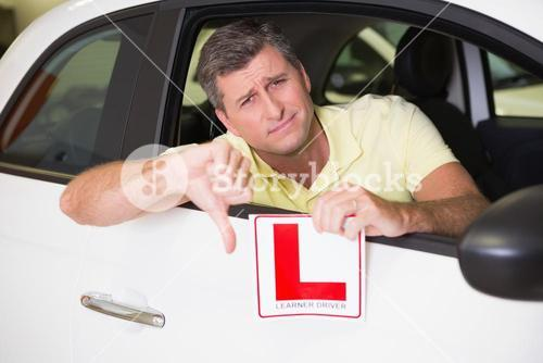 Man gesturing thumbs down holding a learner driver sign
