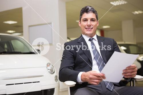 Businessman holding document at his desk