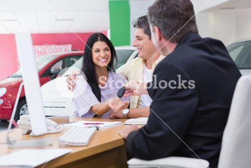 Salesman giving car keys to a couple