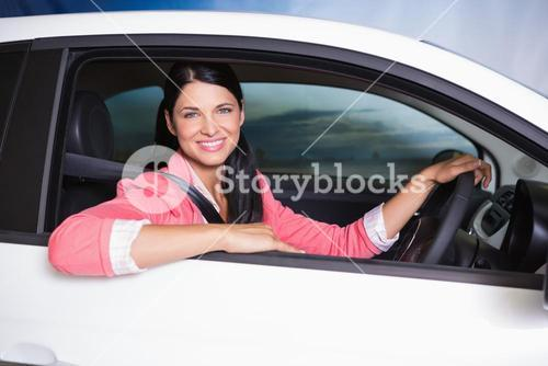 Smiling customer sitting at the wheel of a car for sale