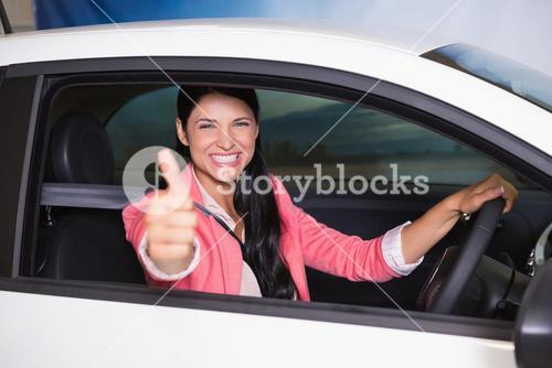 Smiling woman driving while giving thumbs up