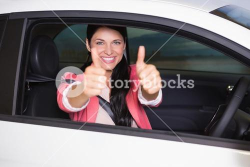 Smiling woman giving thumbs up in her car