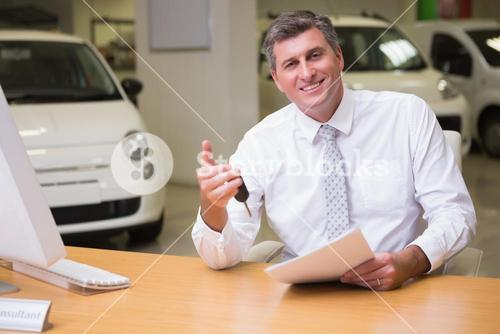 Smiling salesman holding car key and a document