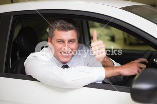 Smiling man sitting in his car giving thumbs up