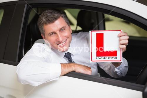 Man holding a learner driver sign sitting behind the wheel