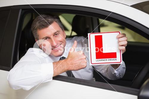 Man gesturing thumbs up holding a learner driver sign