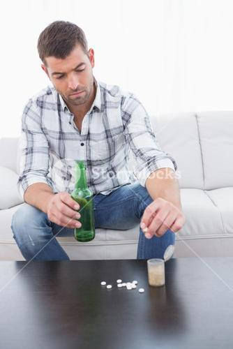 Preoccupied man  with a beer and his medicine laid