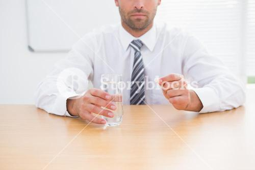 Serious businessman holding glass of water and tablet