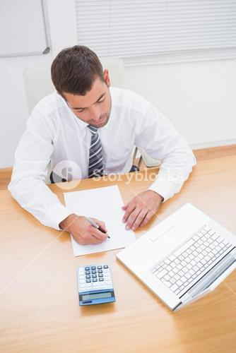Businessman writing on a paper