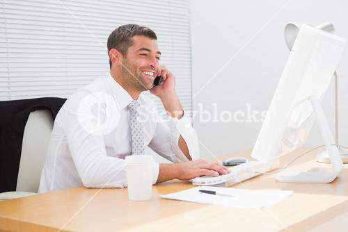 Smiling businessman phoning at his desk