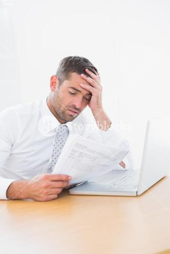 Confused businessman looking at his paper