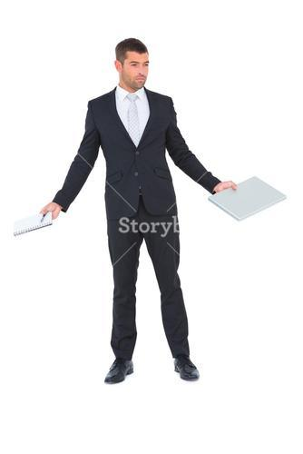 Businessman holding a tablet pc and a notebook