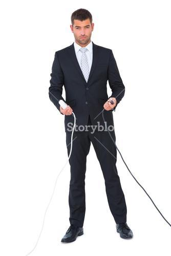 Serious businessman holding cables to connect