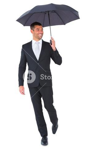 Smiling businessman sheltering under black umbrella