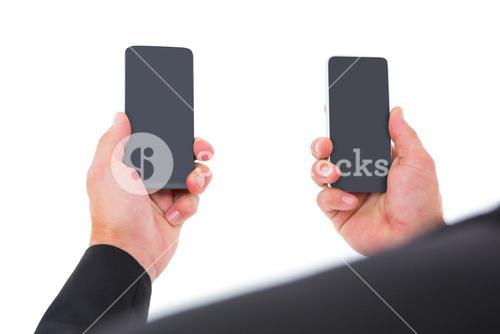 Businessman holding two smart phones
