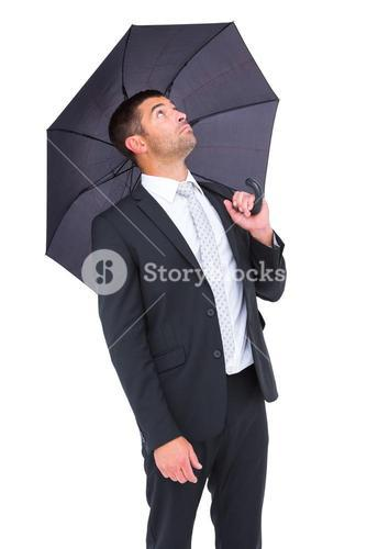 Businessman sheltering under black umbrella