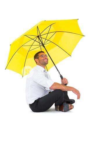 Businessman sitting on the floor with yellow umbrella