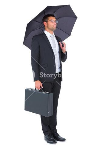 Businessman sheltering under bllack umbrella