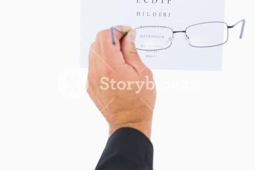 Man holding eyeglasses over paper