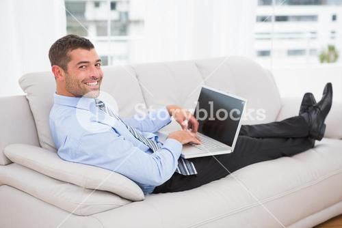 Relaxing businessman on a sofa with a laptop