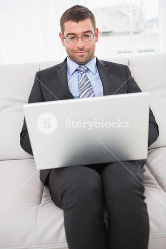 Focused businessman on a sofa with a laptop