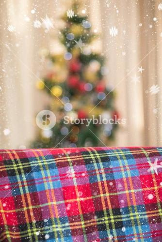 Composite image of warm blanket on the couch at christmas